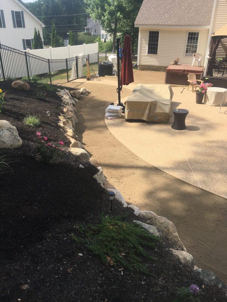 Loam grading around pool, rock wall